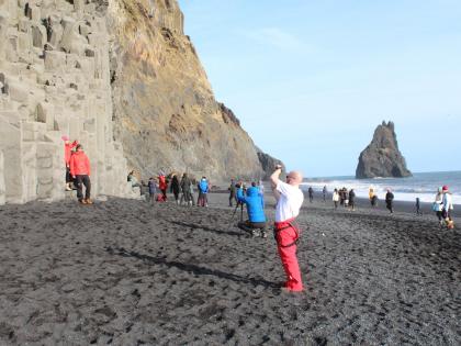 Туристы на черном пляже в Южной Исландии, который известен как
