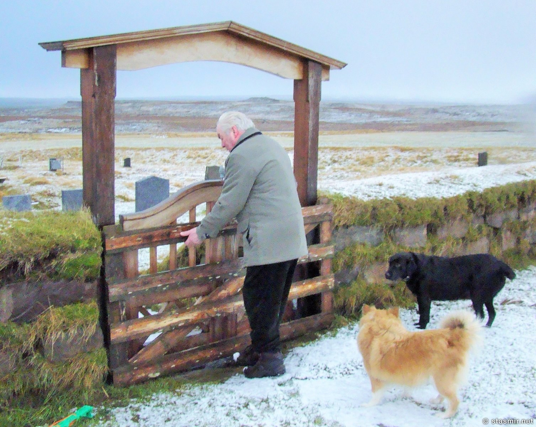 акулий музей Bjarnarhöfn - Hákarlasafnið, Hildibrandur Bjarnason открывает ворота частного кладбища и капеллы, рядом две исландских овчарки, фото Стасмир, Photo Stasmir